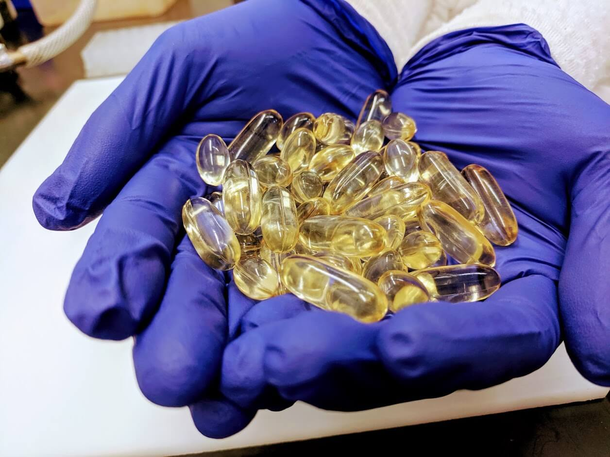 Gloved hands holding vitamin e pills in the testing laboratory